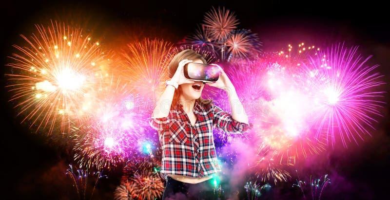 Двойная экспозиция, девушка получая опыт используя стекла VR, находящся в виртуальной реальности, наблюдая фейерверках стоковое изображение