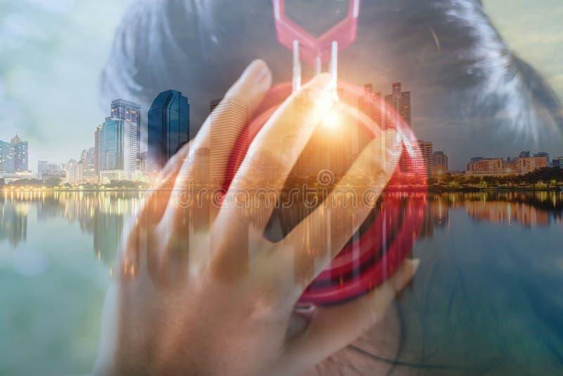 Двойная экспозиция женщины слушая к музыке и городскому пейзажу в солнце стоковая фотография
