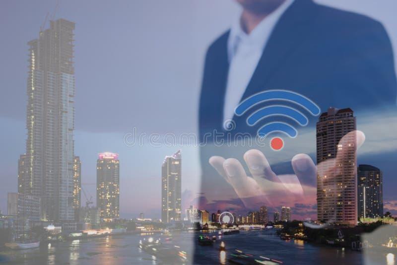 Двойная экспозиция концепции дела, технологии и интернет-связи Бизнесмен используя wifi значка в наличии и современный город стоковая фотография rf