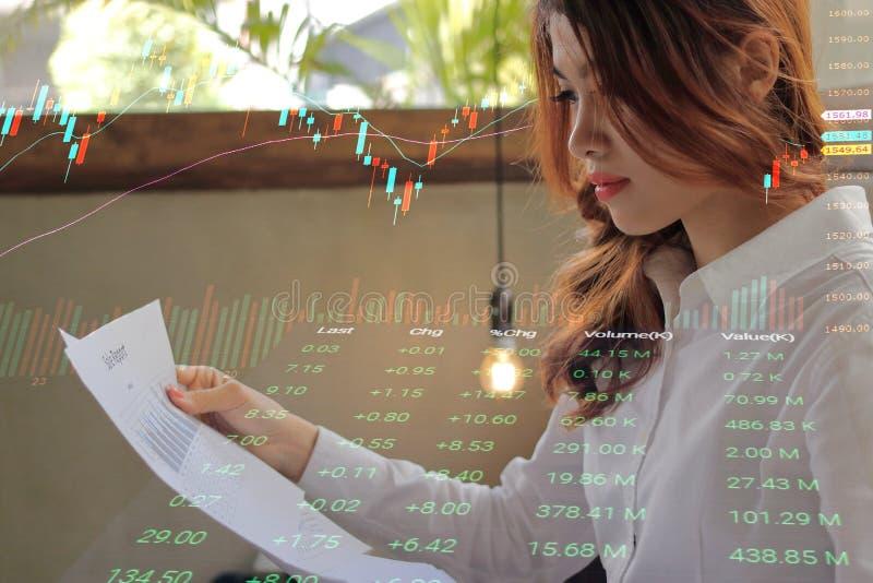 Двойная экспозиция молодой привлекательной азиатской коммерсантки анализируя диаграммы на обработке документов в офисе с подсвечн стоковая фотография