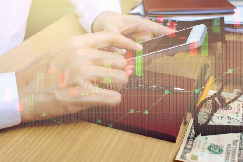 Двойная экспозиция smartphone пользы бизнесмена с фондовой биржей стоковые изображения rf
