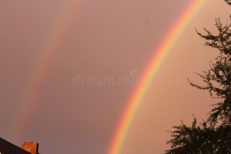 Двойная яркая радуга с бурными небом и крышей стоковая фотография