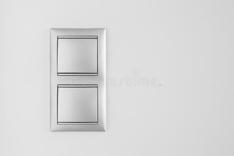Двойной металлический выключатель над белой стеной скопируйте космос иллюстрация штока