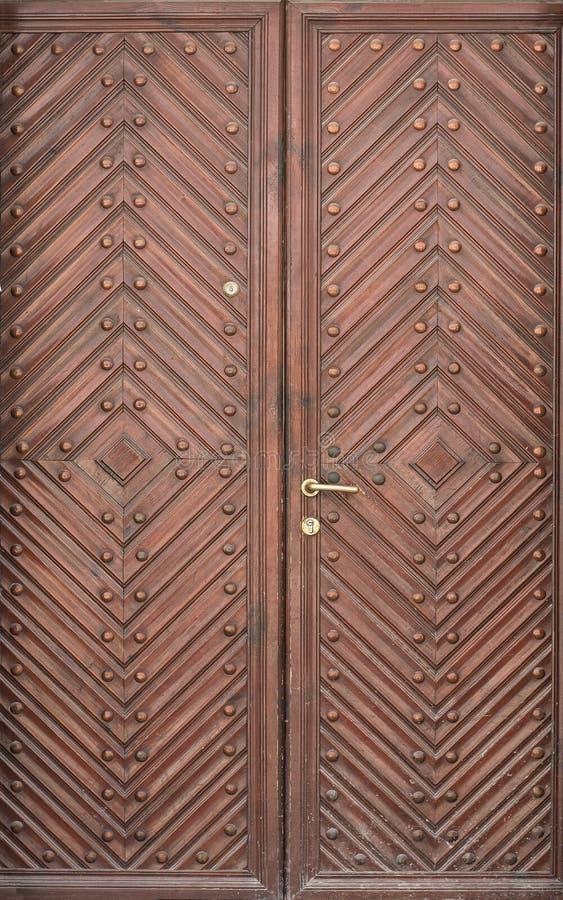 Двойные деревянные двери с диамантом и заклепками Краснокоричневый цвет стоковая фотография rf