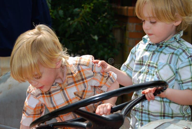 Двойные молодые мальчики пробуют управлять слишком большим колесом стоковое фото rf