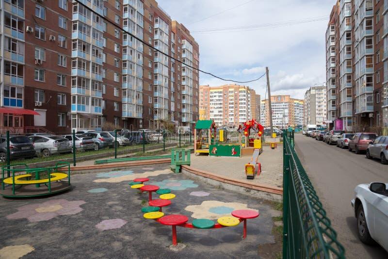 Двор между жилыми домами, с спортивной площадкой детей и припаркованными автомобилями в городе Krasnoyarsk стоковые фото