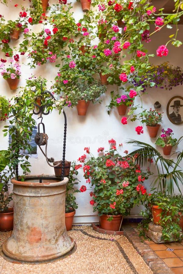 Двор с украшенными цветками и старым колодцем стоковая фотография
