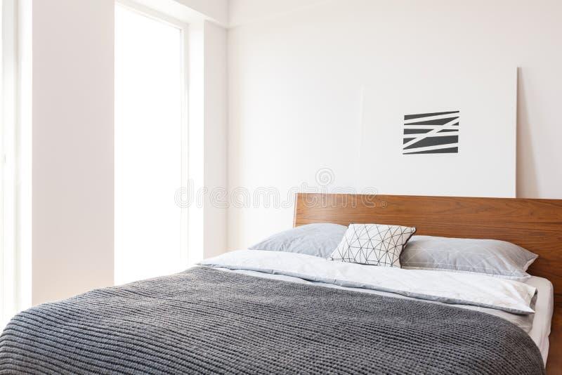 Двуспальная кровать с серыми одеялом и подушками установила в interi спальни стоковое фото rf
