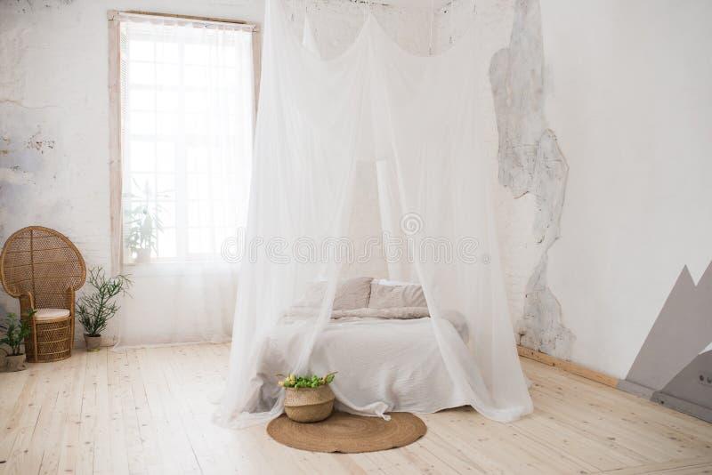 Двуспальная кровать с серыми постельным бельем и сенью beefburgers Плетеный стул сделанный из древесины в угле комнаты стоковые фото