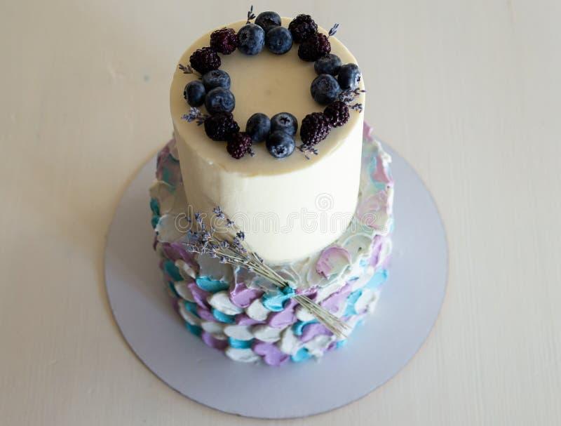 Двухярусный торт сливк в цветах сине-сер-сирени, украшенных с голубиками и sprigs лаванды на черной стойке r стоковые фотографии rf