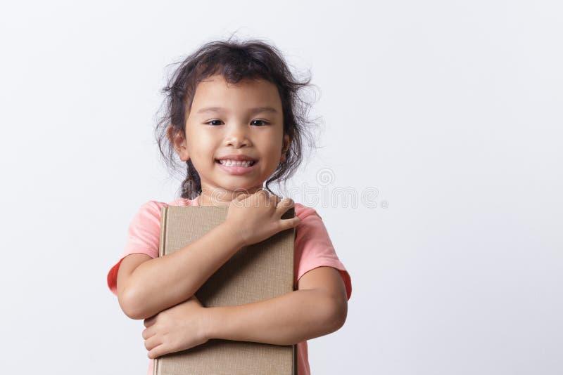 Девочка азиатского происхождения держит коричневую книгу и улыбается, стоя на белом фоне стоковое изображение