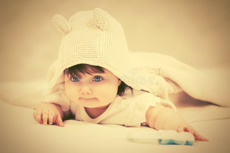 Девочка в толстовке, ползающая на одеяле в толстовке стоковое изображение rf
