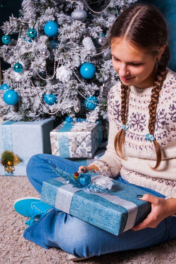 Девочка держа подарок Xmas в руках близко украсила рождественскую елку и камин ели стоковая фотография