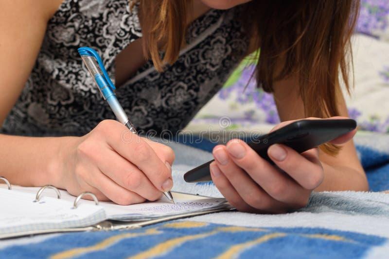 Девочка записывает информацию с экрана смартфона в записную книжку стоковая фотография rf