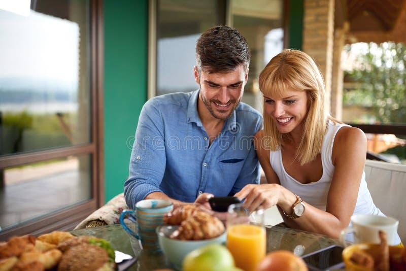 Девочка и парень смотрят на мобильный телефон стоковые изображения rf