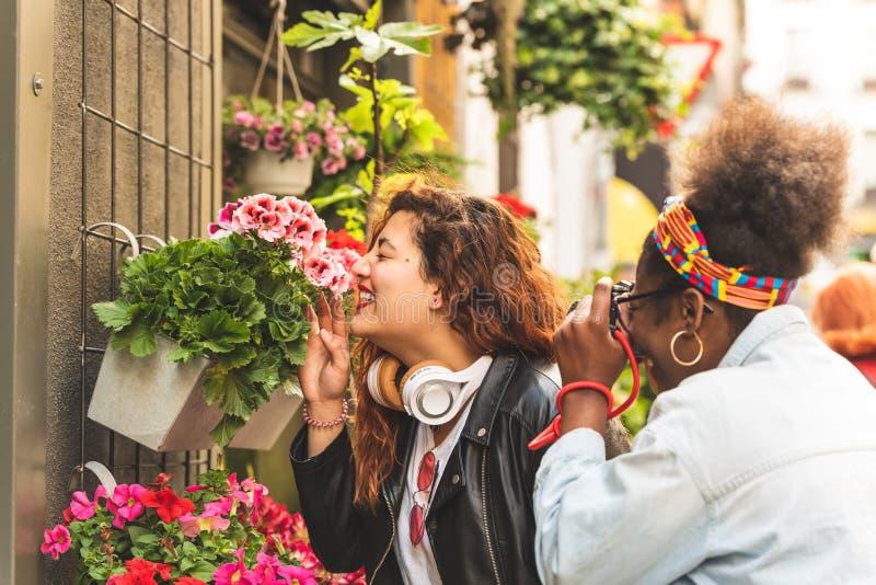 2 девочка-подростка пахнуть цветками стоковая фотография