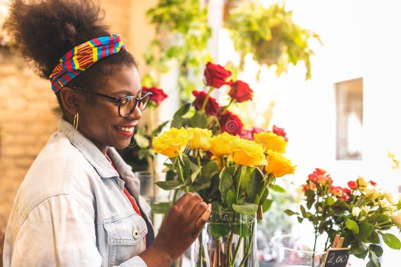 Девочка-подростки Афро американские пахнуть желтыми розовыми цветками стоковое изображение rf