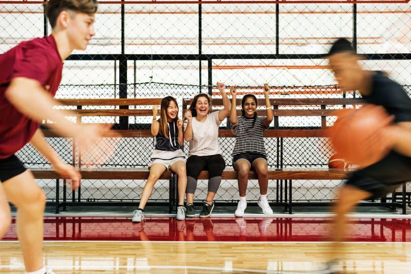 Девочка-подростки веселя мальчиков играя баскетбол стоковое фото rf