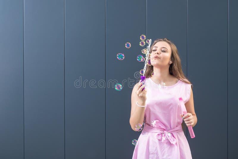 Девочка-подросток в пузырях мыла красивого платья дуя стоковая фотография