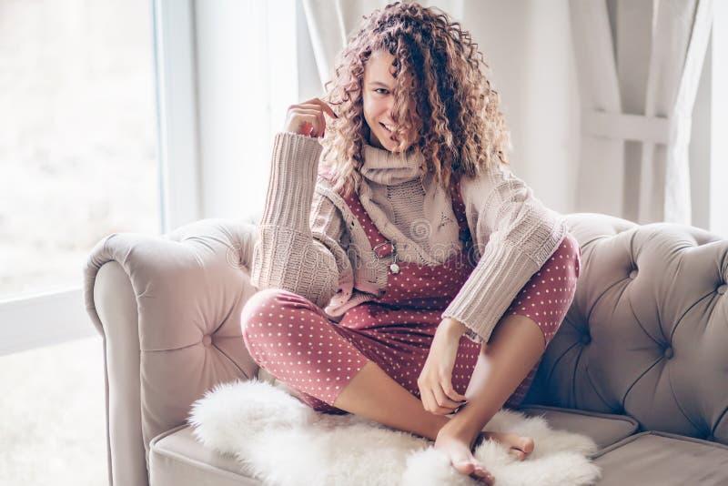 Девочка-подросток в свитере и комбинезоне на кресле стоковые фото
