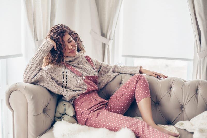Девочка-подросток в свитере и комбинезоне на кресле стоковое изображение rf