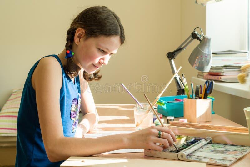 Девочка-подросток дома приниманнсяые за творческие способности, рисует акварель на таблице в комнате стоковое изображение