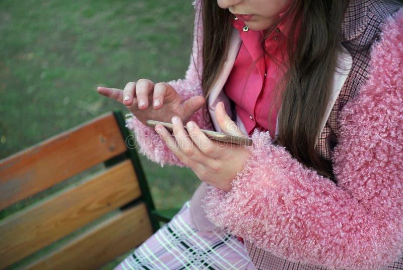 Девочка-подросток занятый с ее мобильным телефоном стоковое фото
