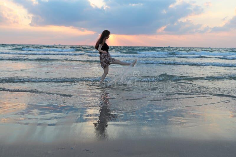 Девочка-подросток идет в воду на заходе солнца стоковое изображение rf