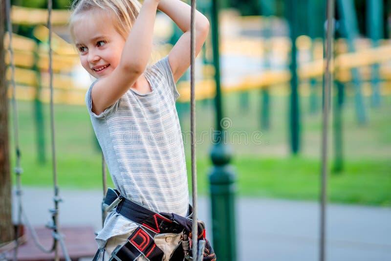 Девочка-подросток идет на прикрепленный на петлях след в парке веревочки стоковые изображения