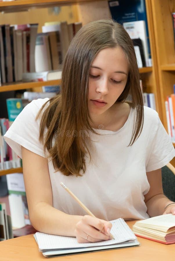 Девочка-подросток изучая в библиотеке стоковые фотографии rf