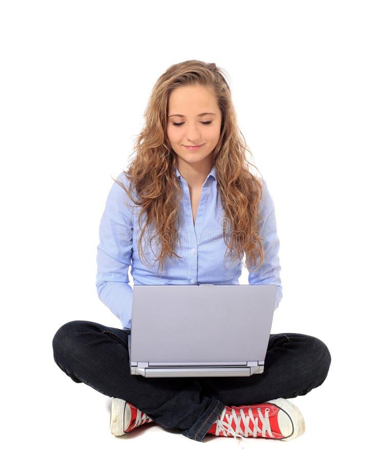 Девочка-подросток используя компьтер-книжку стоковое изображение