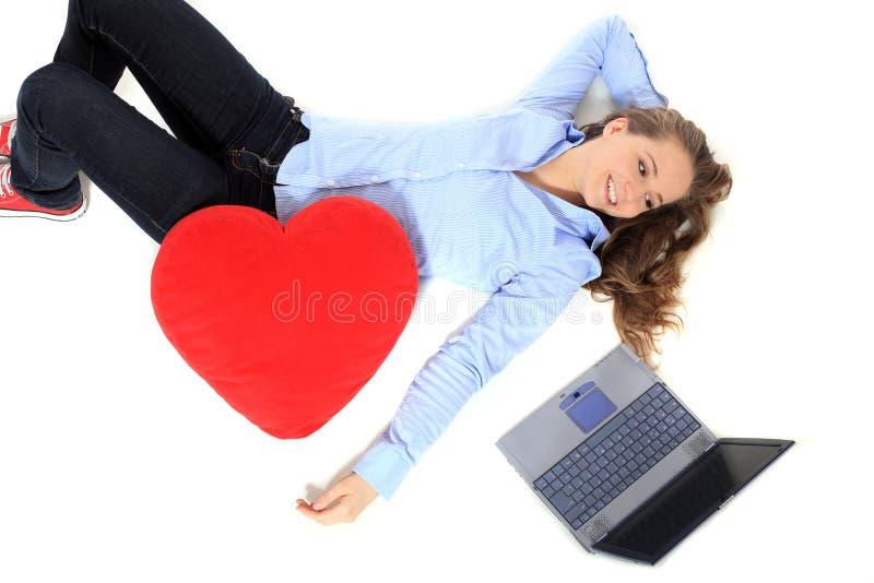 Девочка-подросток лежа рядом с ее компьтер-книжкой стоковое изображение rf
