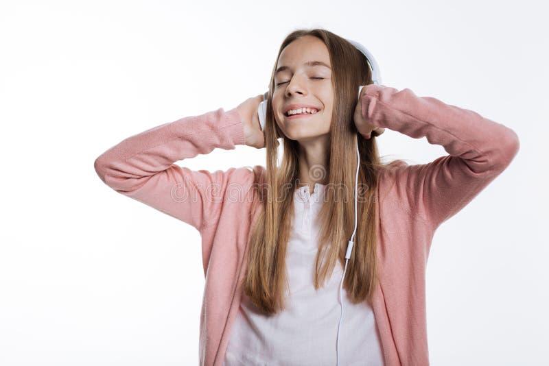 Девочка-подросток наслаждаясь любимыми песнями в наушниках стоковая фотография