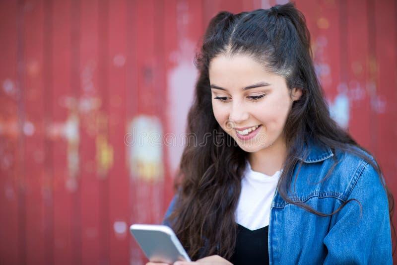 Девочка-подросток отправляя СМС на мобильном телефоне в городских условиях стоковая фотография rf