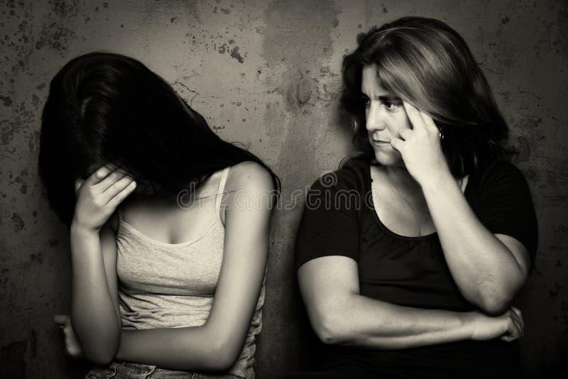 Девочка-подросток плачет рядом с ее сердитой и потревоженной матерью стоковое фото rf