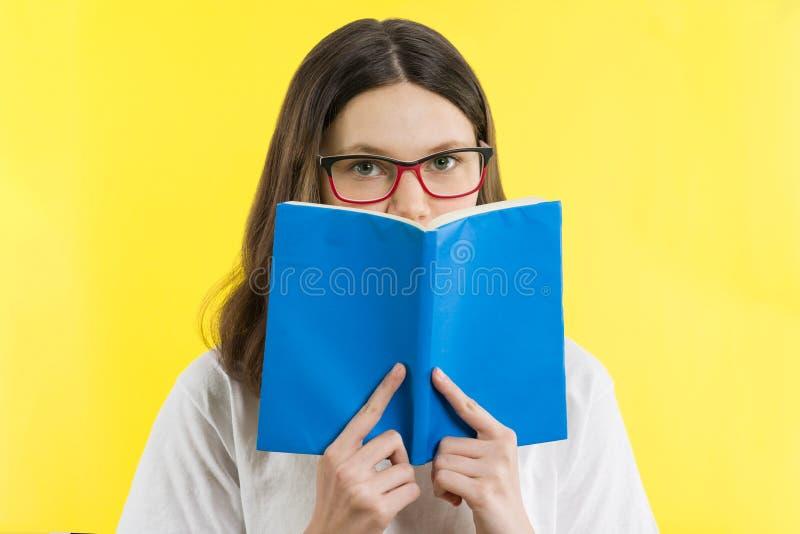 Девочка-подросток портрета крупного плана при стекла рассматривая книга, желтая предпосылка глаза стоковые изображения rf