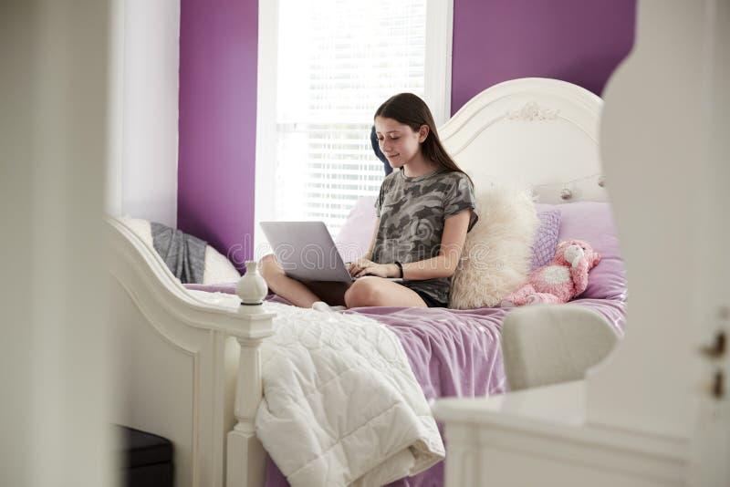 Девочка-подросток сидя на ее кровати используя портативный компьютер стоковое фото