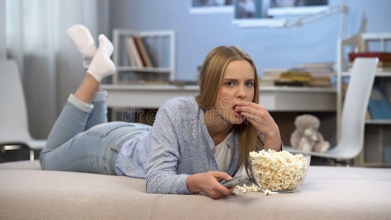 Девочка-подросток смотря интересный фильм по телевизору и есть попкорн, отдых стоковые фотографии rf
