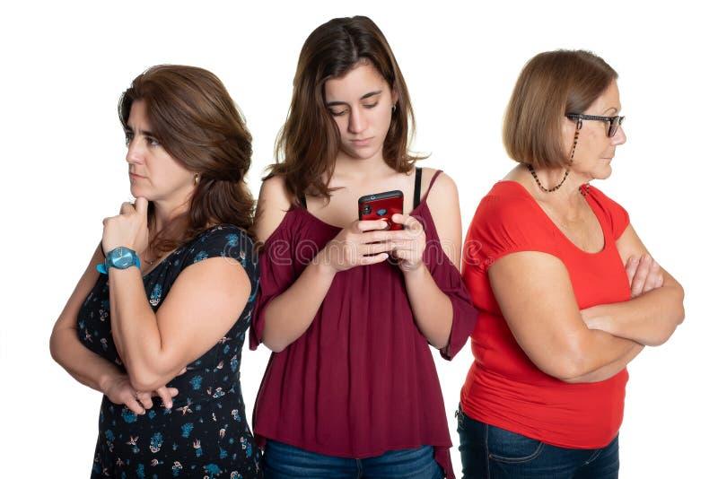 Девочка-подросток телефона пристрастившийся с ее потревоженными матерью и бабушкой стоковое фото