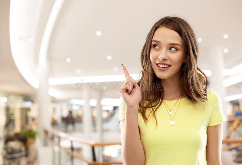 Девочка-подросток указывая палец вверх в торговом центре стоковая фотография rf