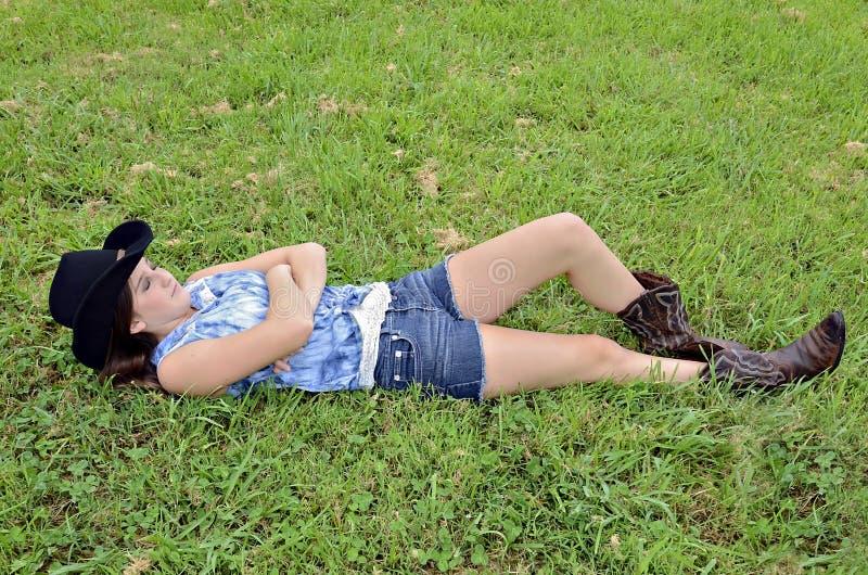Девочка-подросток лежа в траве стоковое изображение