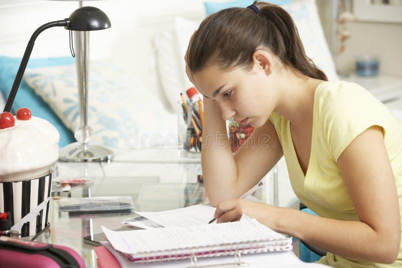 Девочка-подросток изучая на столе в спальне стоковое изображение
