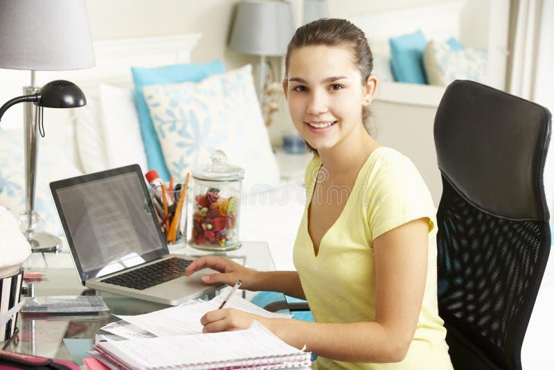 Девочка-подросток изучая на столе в спальне стоковое фото