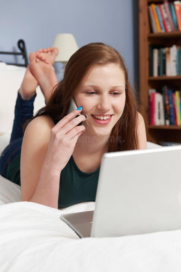 Девочка-подросток используя компьтер-книжку и мобильный телефон в спальне стоковые изображения rf