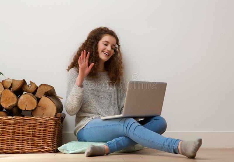 Девочка-подросток используя компьтер-книжку и развевающ здравствуйте! на болтовне стоковая фотография