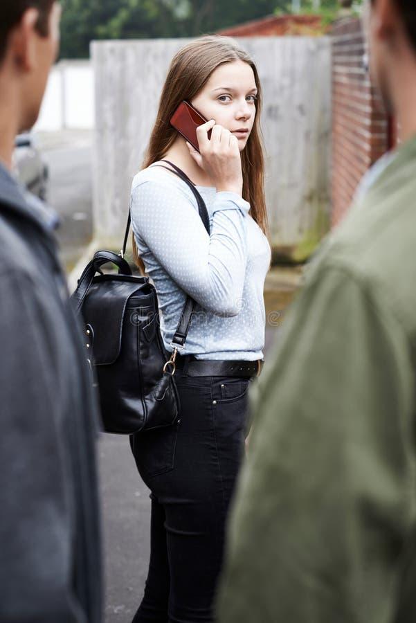 Девочка-подросток используя мобильный телефон чувствует запуганным по мере того как она идет домой стоковое фото rf