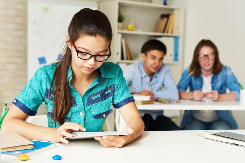 Девочка-подросток используя таблетку в современном классе стоковое изображение rf