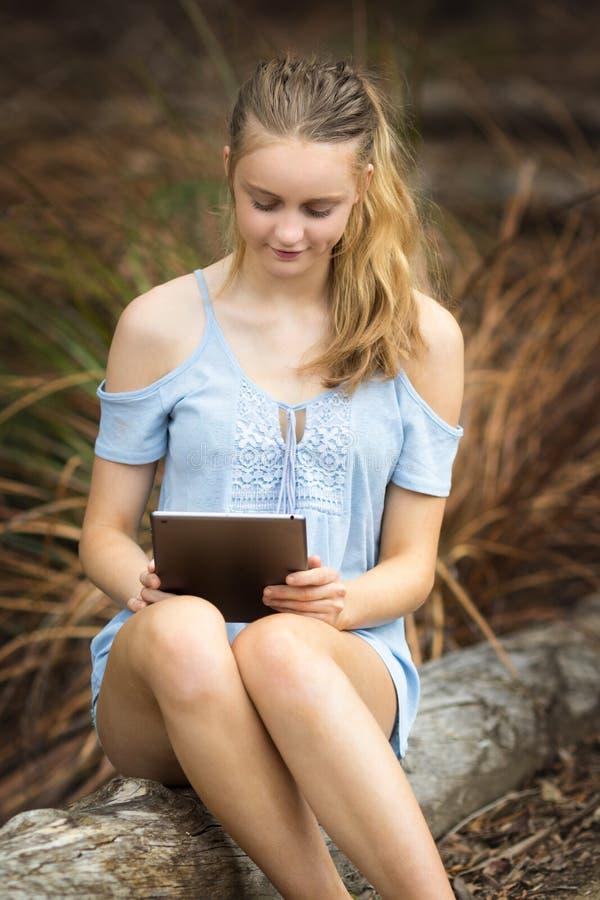 Девочка-подросток используя таблетку стоковые фото