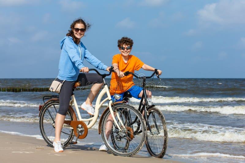 Девочка-подросток и мальчик велосипед на пляже стоковое фото rf