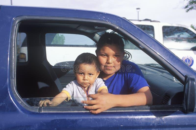 Девочка-подросток и младенец Навахо смотря из окна автомобиля, Kayenta, AZ стоковые изображения rf